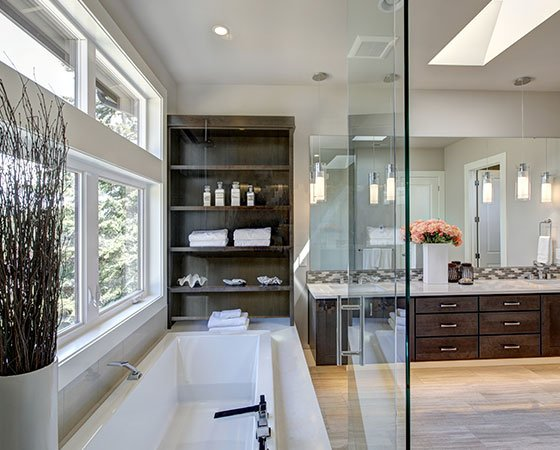 Large, modern bathroom with large windows, white tub with glass wall, double sink with dark brown cabinets, and large mirror.