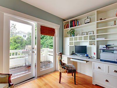 Cozy home office with large glass doors, bright hardwood flooring, white furniture, and greenish painted walls.