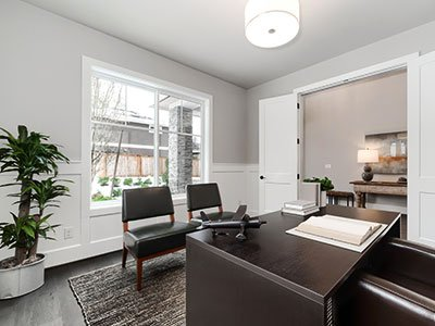 Simple style home office room, with light gray painted walls, dark wooden desk, dark leather chairs, striped carpet, and large windows.