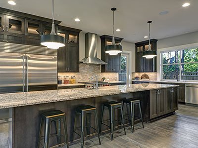 Large kitchen with dark wooden cabinets, silver finish appliances, black chairs, and large island with beige quartz countertop.