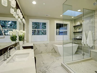 Large bathroom with double sink, large mirror, white lights, marble floor, white tub, and glass shower tower.