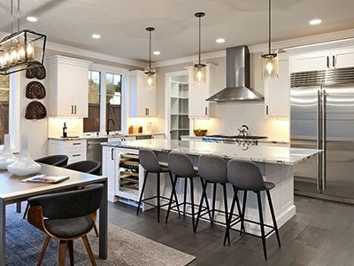 Medium-sized kitchen with gray chairs, white cabinets, large island with quartz countertop, and warm lights.