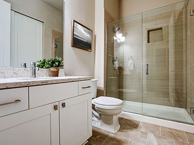 Medium-sized bathroom with white painted cabinets, quartz countertop, brown tiles floor, and shower with glass doors.