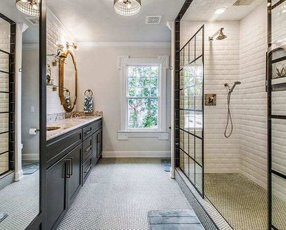 Luxury bathroom, with dark cabinets, quartz countertop, golden mirror, warm lights, and large shower with glass doors.