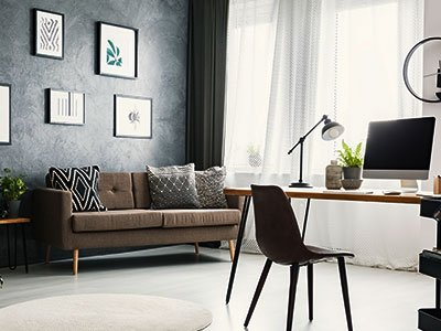 Modern home office with brown couch, wooden desk, lamp, large windows, and dark gray painted meeting wall.
