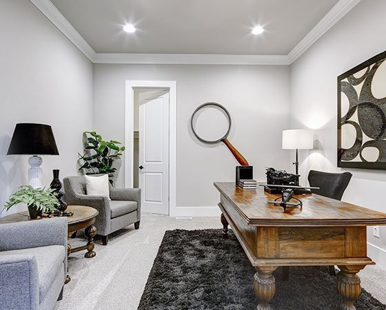 Modern home office room, with gray armchairs, wooden desk, light gray walls, and dark gray carpet.