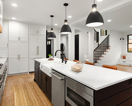 Modern luxurious kitchen with black island and overhang lights
