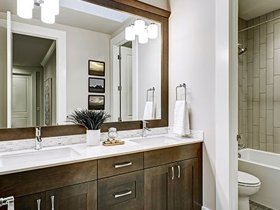 Small modern bathroom, with white lights, white tub, dark wooden cabinets, and large mirror.
