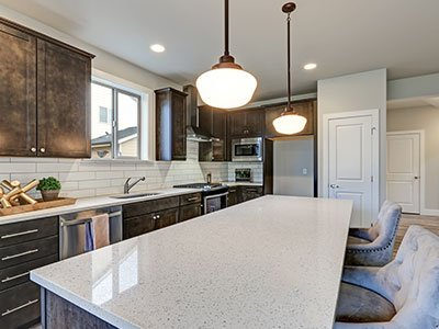 Modern kitchen with dark brown cabinets, large island with quartz countertop, metal chairs, and warm lighting.